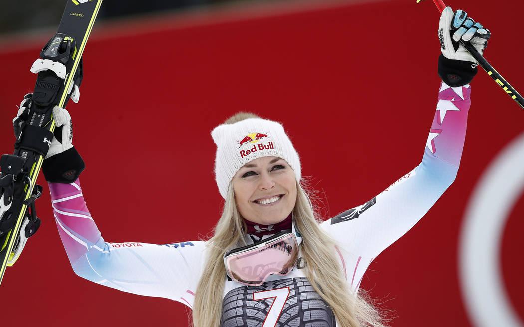 United States' Lindsey Vonn celebrates on the podium after winning an alpine ski, women's world Cup downhill race, in Garmisch Partenkirchen, Germany, Sunday, Feb. 4, 2018. (AP Photo/Gabriele Facc ...