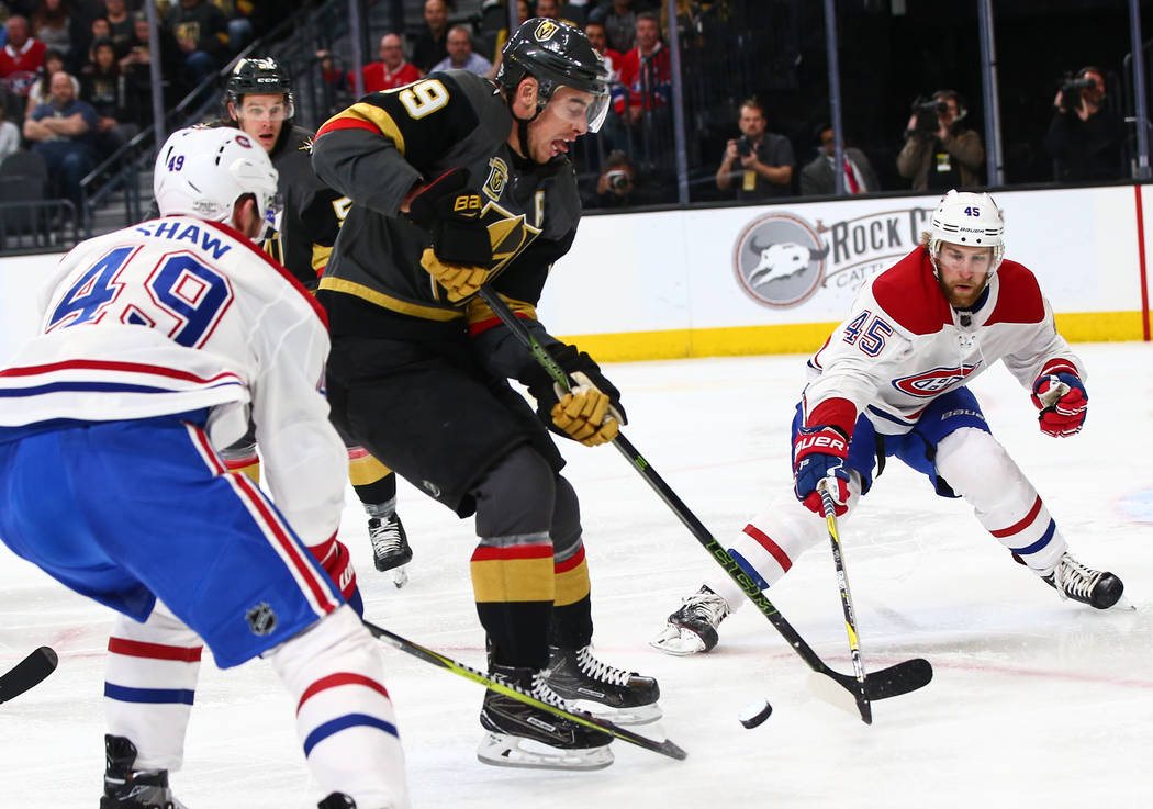 Golden Knights right wing Reilly Smith (19) tries to get past Montreal Canadiens right wing Logan Shaw (49) and defenseman Joe Morrow (45) during an NHL hockey game at T-Mobile Arena in Las Vegas  ...