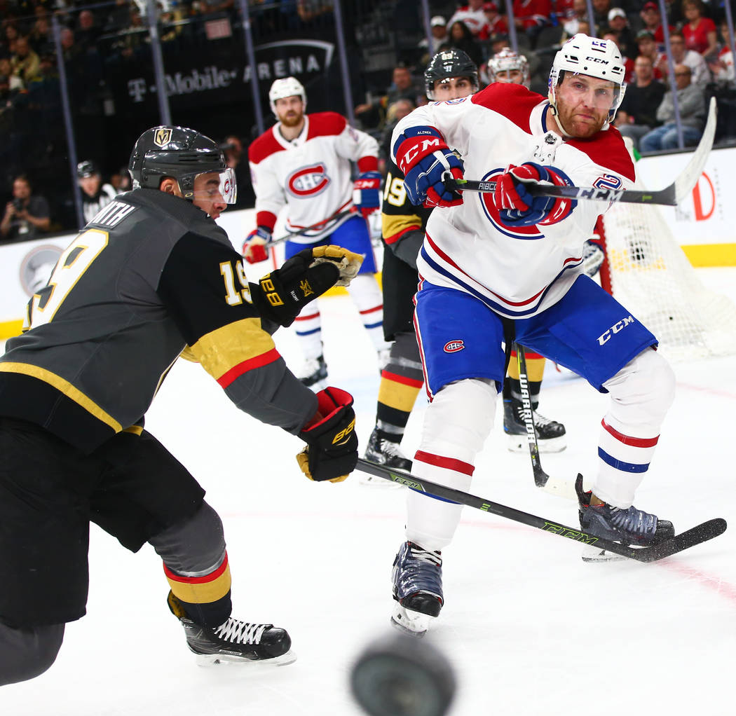 Montreal Canadiens defenseman Karl Alzner (22) bounces the puck off the glass past Golden Knights right wing Reilly Smith (19) during the first period of an NHL hockey game at T-Mobile Arena in La ...