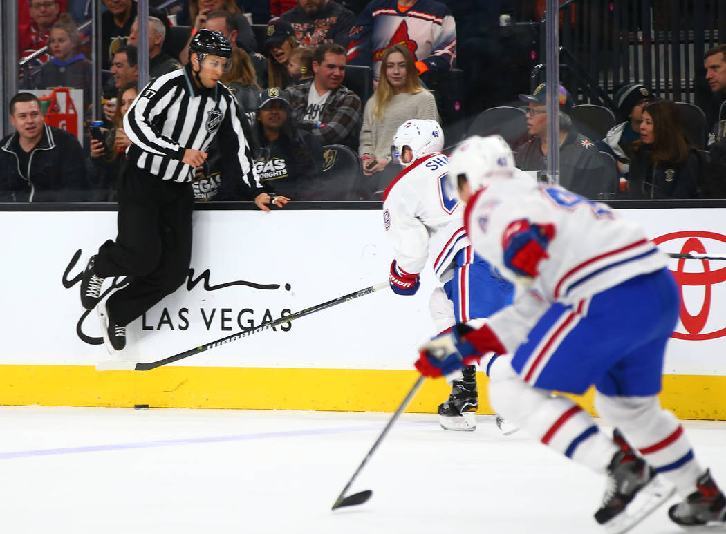A referee dodges the puck as the Golden Knights play the Montreal Canadiens during the first period of an NHL hockey game at T-Mobile Arena in Las Vegas on Saturday, Feb. 17, 2018. Chase Stevens L ...