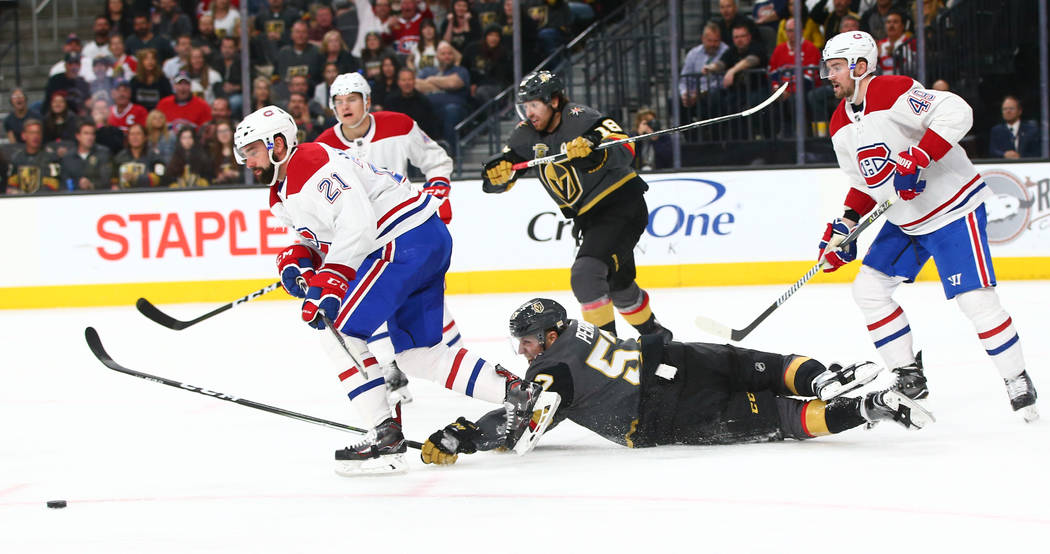Golden Knights left wing David Perron (57) falls to the ice as Montreal Canadiens defenseman David Schlemko (21) goes after the puck during the third period of an NHL hockey game at T-Mobile Arena ...