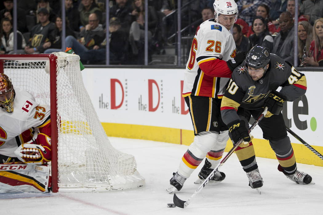 Vegas Golden Knights center Ryan Carpenter (40) looks for an open shot against pressure from Calgary Flames defenseman Michael Stone (26)during the first period of an NHL game  at T-Mobile Arena i ...