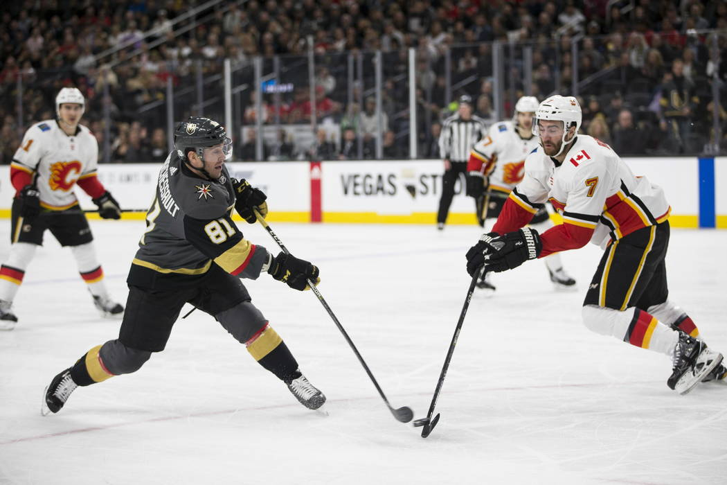 Vegas Golden Knights center Jonathan Marchessault (81) shoots the puck against pressure from Calgary Flames defenseman TJ Brodie (7) during the first period of an NHL game  at T-Mobile Arena in La ...