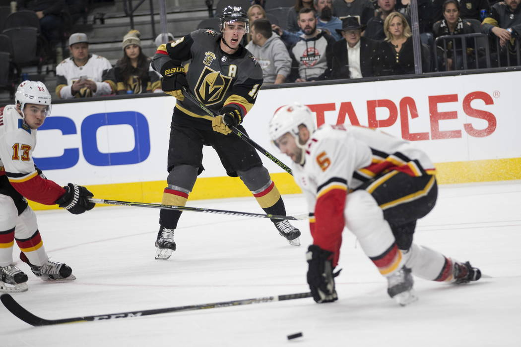 Vegas Golden Knights right wing Reilly Smith (19) makes a pass under pressure from Calgary Flames defenseman Mark Giordano (5) during the first period of an NHL game  at T-Mobile Arena in Las Vega ...