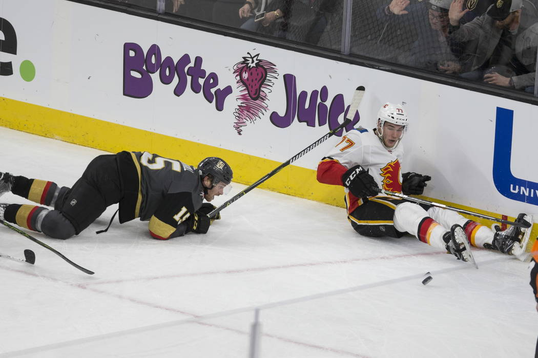 Vegas Golden Knights defenseman Jon Merrill (15) and Calgary Flames center Mark Jankowski (77) fall on the ice while fighting for the puck during the second period of an NHL hockey game at T-Mobil ...