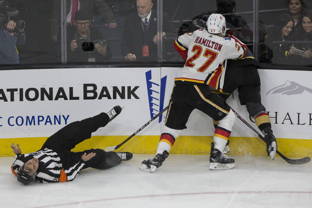 A referee takes a fall during a hard play between Vegas Golden Knights left wing Erik Haula (56) and Calgary Flames defenseman Dougie Hamilton (27) in the second period of an NHL hockey game at T- ...