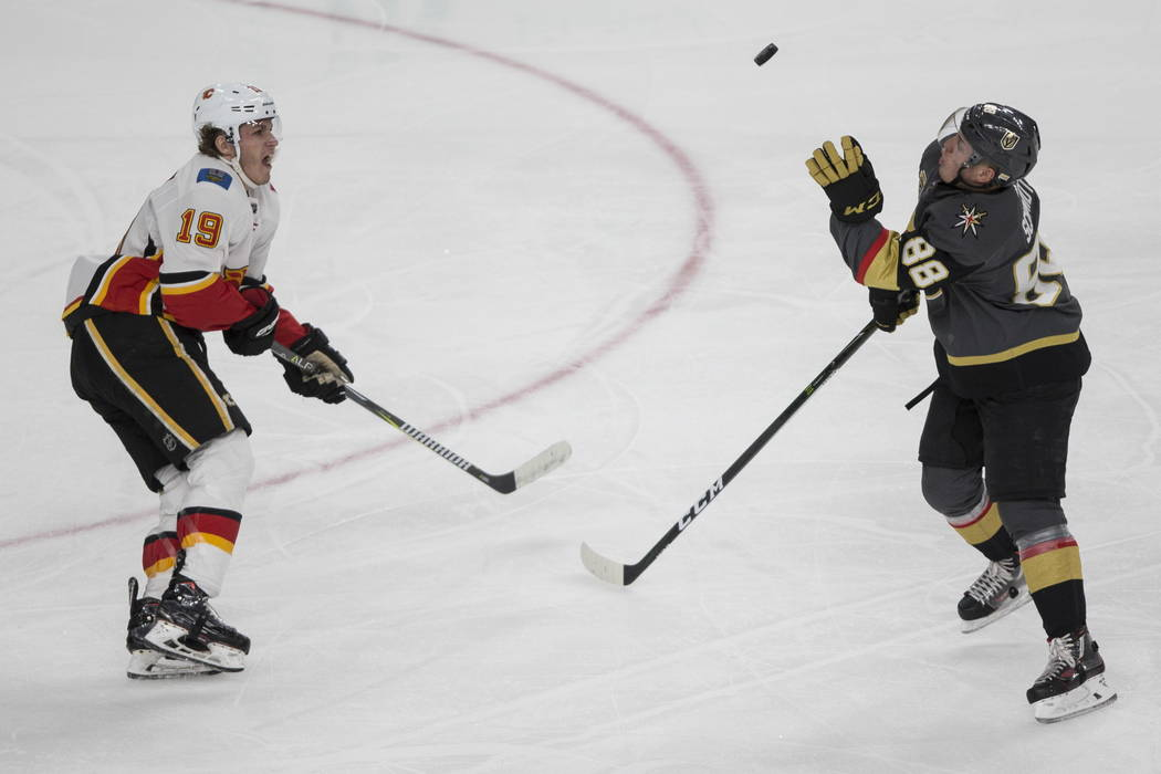 Vegas Golden Knights defenseman Nate Schmidt (88) reach for the puck against pressure from Calgary Flames left wing Matthew Tkachuk (19) during the second period of an NHL hockey game at T-Mobile  ...