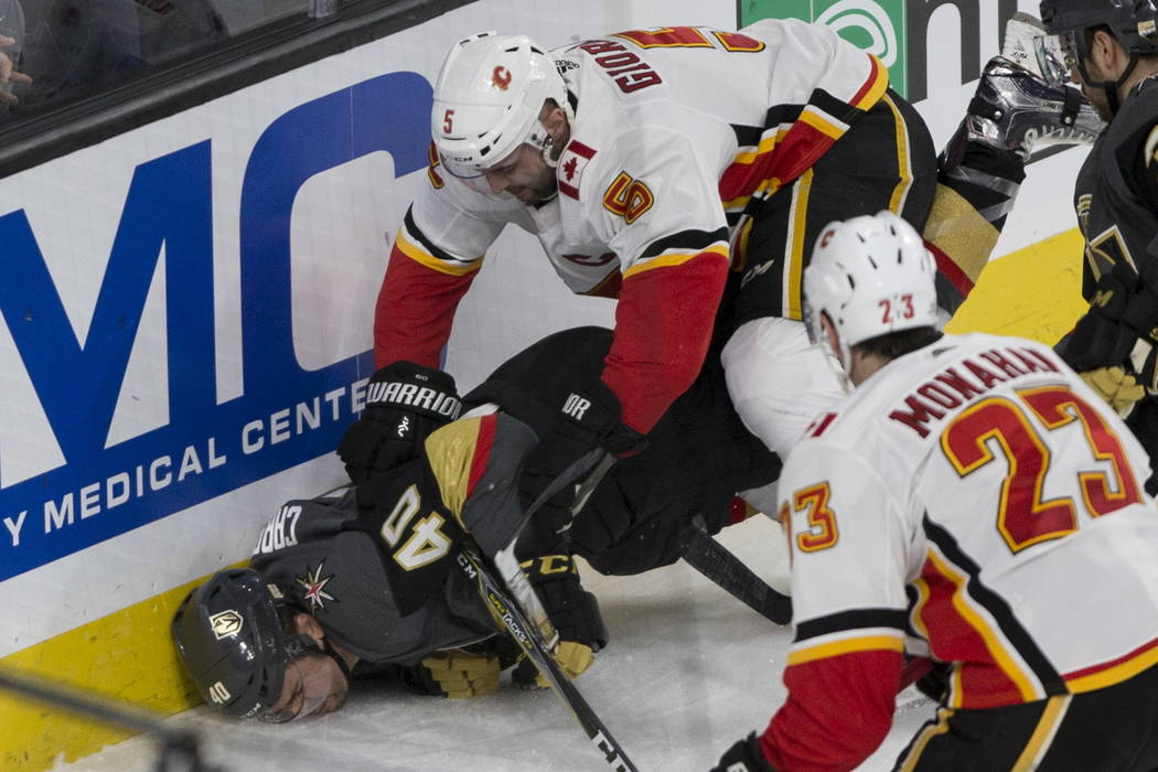 Vegas Golden Knights center Ryan Carpenter (40) is pushed down to the ice against Calgary Flames defenseman Mark Giordano (5) during the second period of an NHL hockey game at T-Mobile Arena in La ...