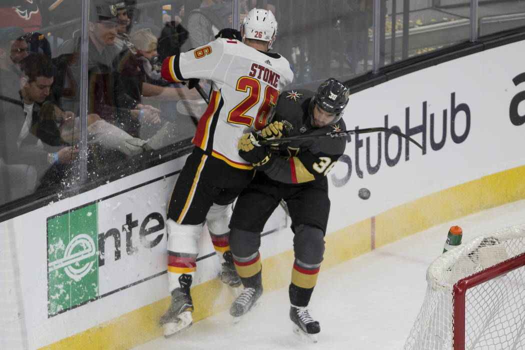 Vegas Golden Knights right wing Tomas Hyka (38) fights for posession against Calgary Flames defenseman Michael Stone (26) during the second period of an NHL hockey game at T-Mobile Arena in Las Ve ...