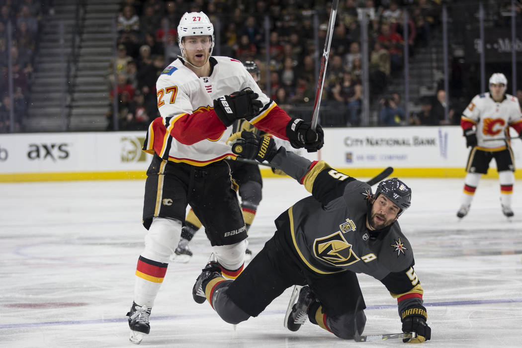 Vegas Golden Knights defenseman Deryk Engelland (5) takes a fall going for the puck against Calgary Flames defenseman Dougie Hamilton (27) during the third period of an NHL game at T-Mobile Arena  ...
