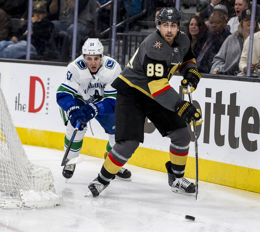 Golden Knights right wing Alex Tuch (89) tries to keep the puck away from Vancouver Canucks defenseman Troy Stecher (51) while looking for a pass during the first period of an NHL hockey game at T ...