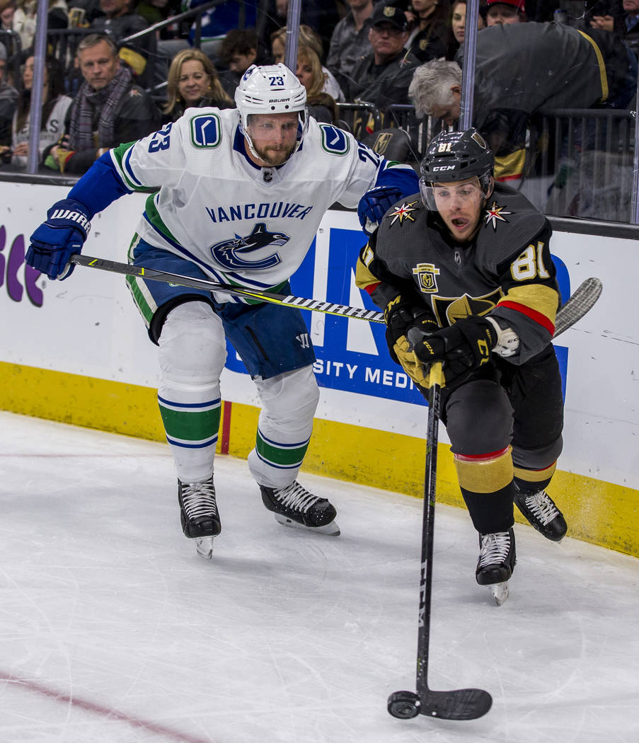 Golden Knights center Jonathan Marchessault (81) and Vancouver Canucks defenseman Alexander Edler (23) chase after the puck during the first period of an NHL hockey game at T-Mobile Arena in Las V ...