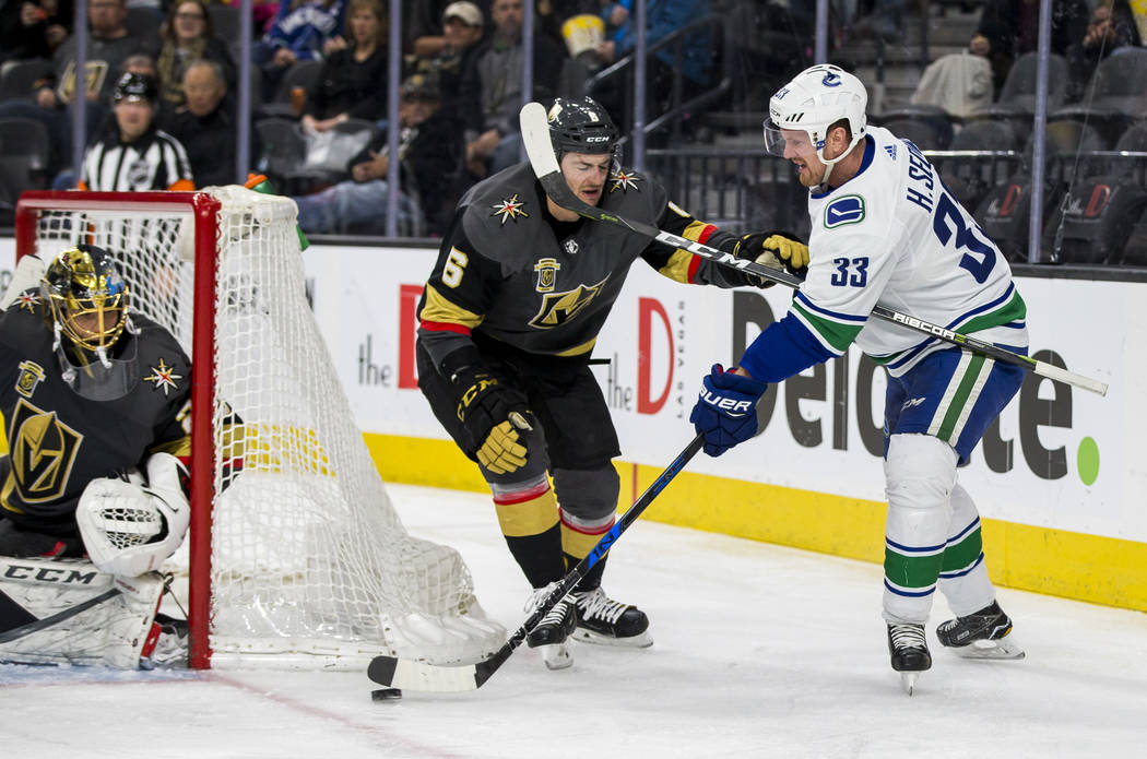 Vancouver Canucks center Henrik Sedin (33) tries to shovel the puck towards the goal while trying to ward off Golden Knights defenseman Colin Miller (6) with Golden Knights goaltender Marc-Andre F ...