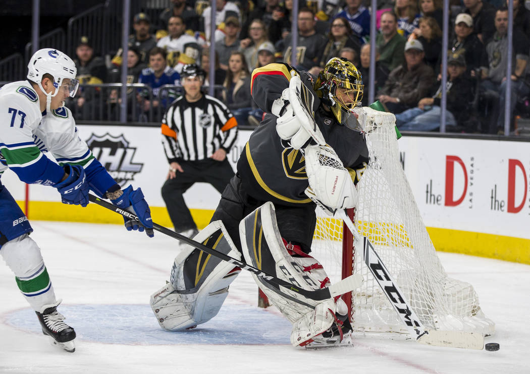 Golden Knights goaltender Marc-Andre Fleury (29) deflects the puck from Vancouver Canucks right wing Nikolay Goldobin (77) during the second period of an NHL hockey game at T-Mobile Arena in Las V ...