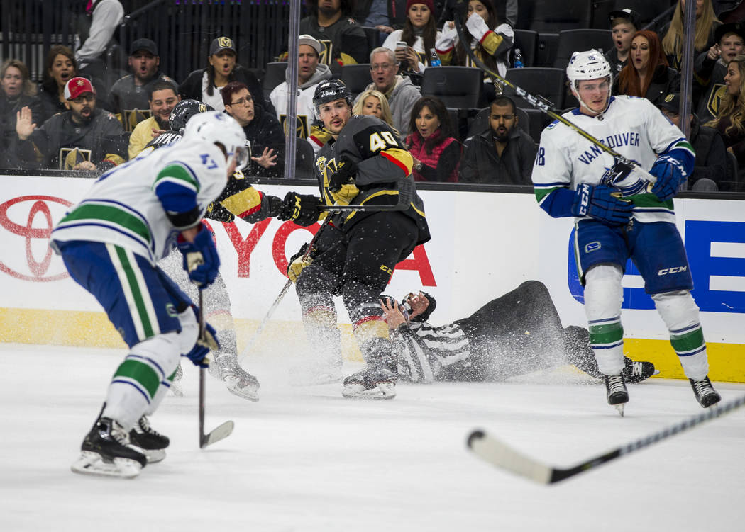 Referee Mark Wheler takes a tumble while Golden Knights center Ryan Carpenter (40), Vancouver Canucks left wing Sven Baertschi (47) and Vancouver Canucks right wing Jake Virtanen (18) search for t ...