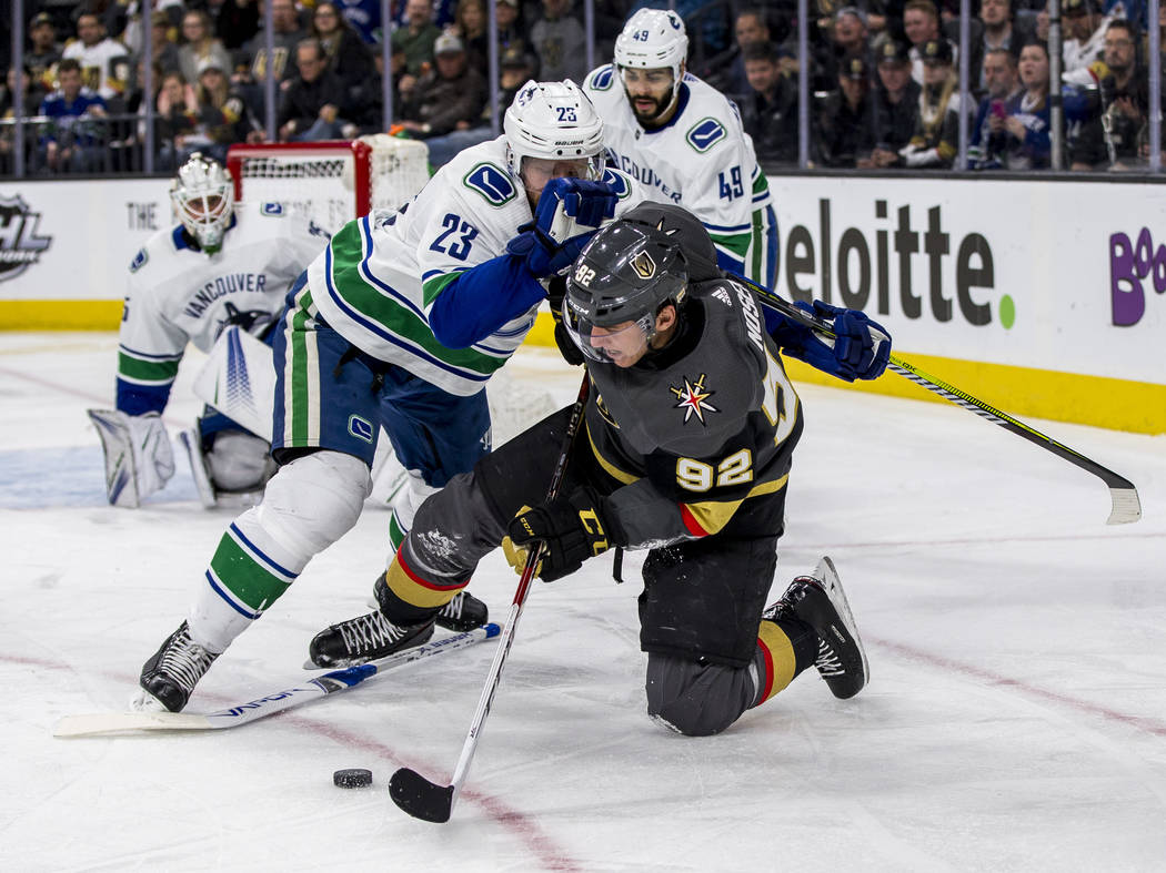Golden Knights left wing Tomas Nosek (92) tries to clear the puck while sliding and warding off Vancouver Canucks defenseman Alexander Edler (23) during the third period of an NHL hockey game at T ...