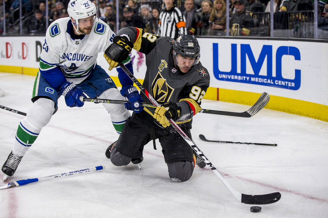 Golden Knights left wing Tomas Nosek (92) tries to clear the puck while on his knees, warding off Vancouver Canucks defenseman Alexander Edler (23) during the third period of an NHL hockey game at ...