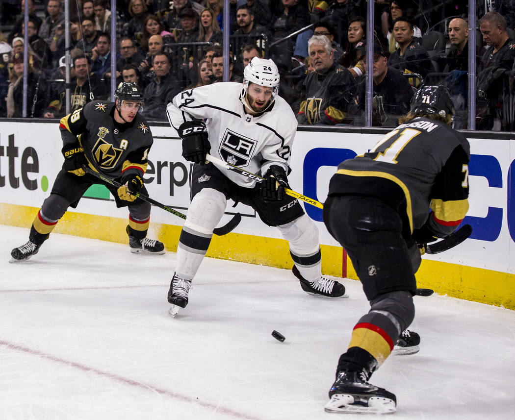 Los Angeles Kings defenseman Derek Forbort (24) tries to get the puck away from Vegas Golden Knights right wing Reilly Smith (19) and Vegas Golden Knights center William Karlsson (71) during the f ...