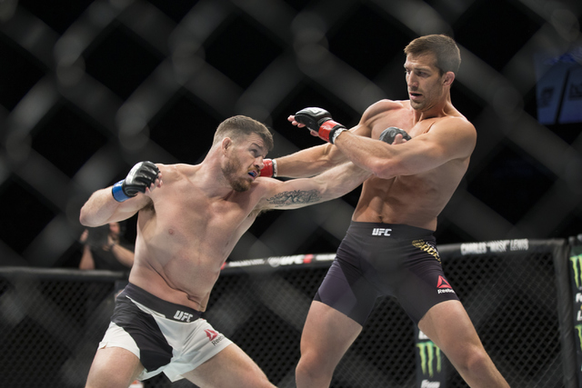 Michael Bisping, left, throws a punch against Luke Rockhold in the UFC 199 middleweight title bout at The Forum on Saturday, June 4, 2016, in Inglewood, Calif. Bisping won by way of knockout in th ...