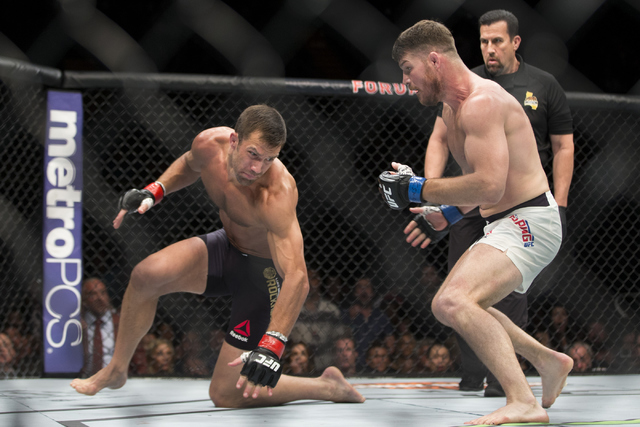 Michael Bisping, right, goes after Luke Rockhold after knocking him down in the UFC 199 middleweight title bout at The Forum on Saturday, June 4, 2016, in Inglewood, Calif. Bisping won by way of k ...