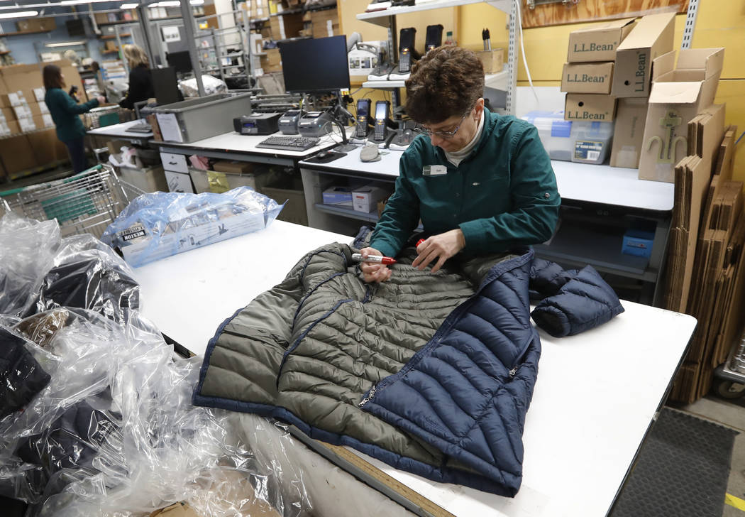In this Friday, Feb. 2, 2018, photo a worker marks a coat that was returned to the LL Bean retail store in Freeport, Maine. L.L. Bean's generous return policy is going to be a little less forgivin ...