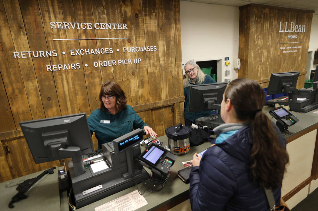 In this Friday, Feb. 2, 2018, photo Dawn Segars accepts a customer's returned items at the LL Bean retail store in Freeport, Maine. L.L. Bean's generous return policy is going to be a little less  ...
