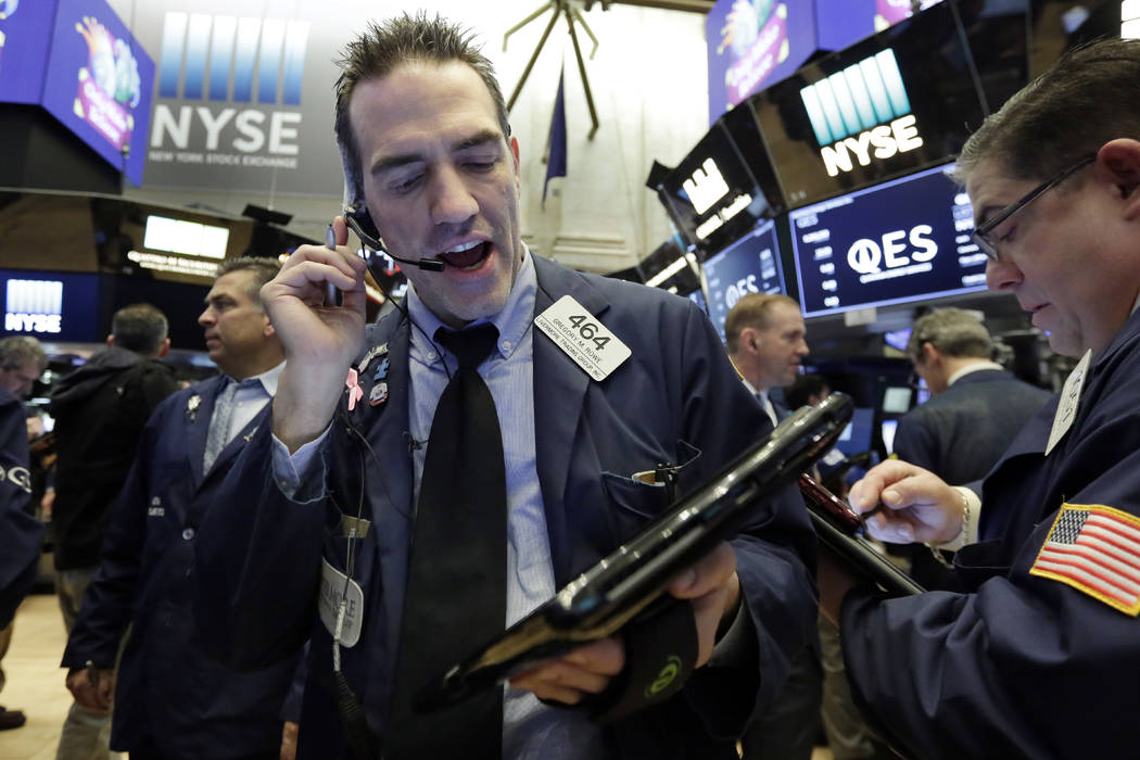 Trader Gregory Rowe, center, works on the floor of the New York Stock Exchange, Friday, Feb. 9, 2018. U.S. stocks wavered between small gains and losses in morning trading Friday, giving up some o ...