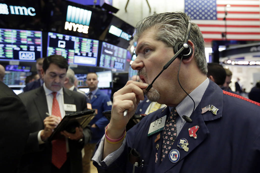 Trader John Panin, right, works on the floor of the New York Stock Exchange, Friday, Feb. 9, 2018. Stocks struggled to stabilize Friday as investors sent prices climbing, then slumping in unsteady ...