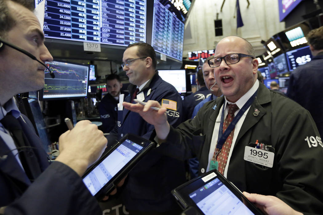 Trader Jeffrey Vazquez, right, works on the floor of the New York Stock Exchange, Friday, Feb. 9, 2018. U.S. stocks wavered between small gains and losses in morning trading Friday, giving up some ...