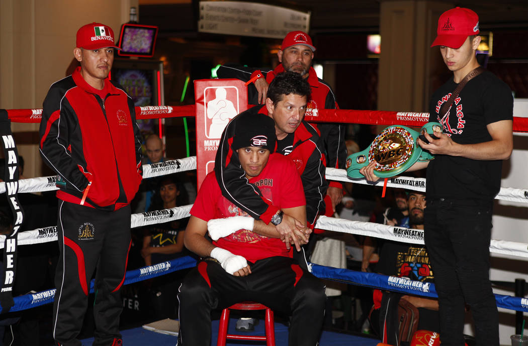 Alex Ariza stretches David Benavidez, sitting, as his father and trainer, Jose Benavidez, Sr., left, looks on during the open workouts at the Mandalay Bay in Las Vegas, Wednesday, Feb. 14, 2018. H ...