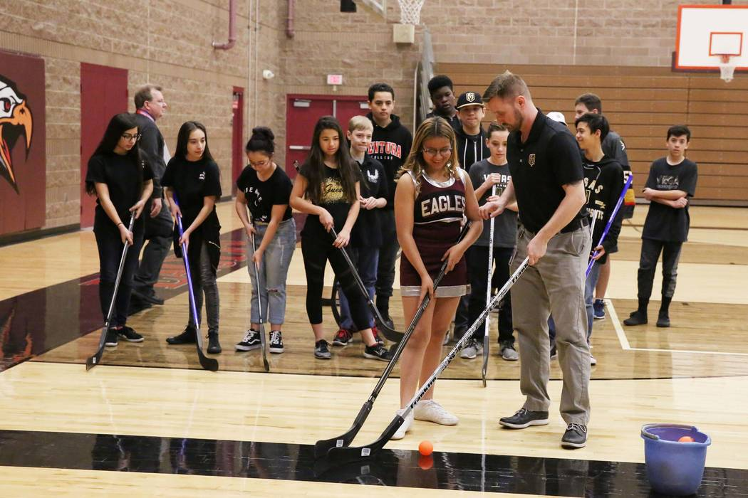 Matt Flynn, Vegas Golden Knights senior manager, youth hockey, right, demonstrates how to hold a hockey stick to Evelyn Murillo at Walter Johnson Junior High School on Monday, Feb. 12, 2018, in La ...