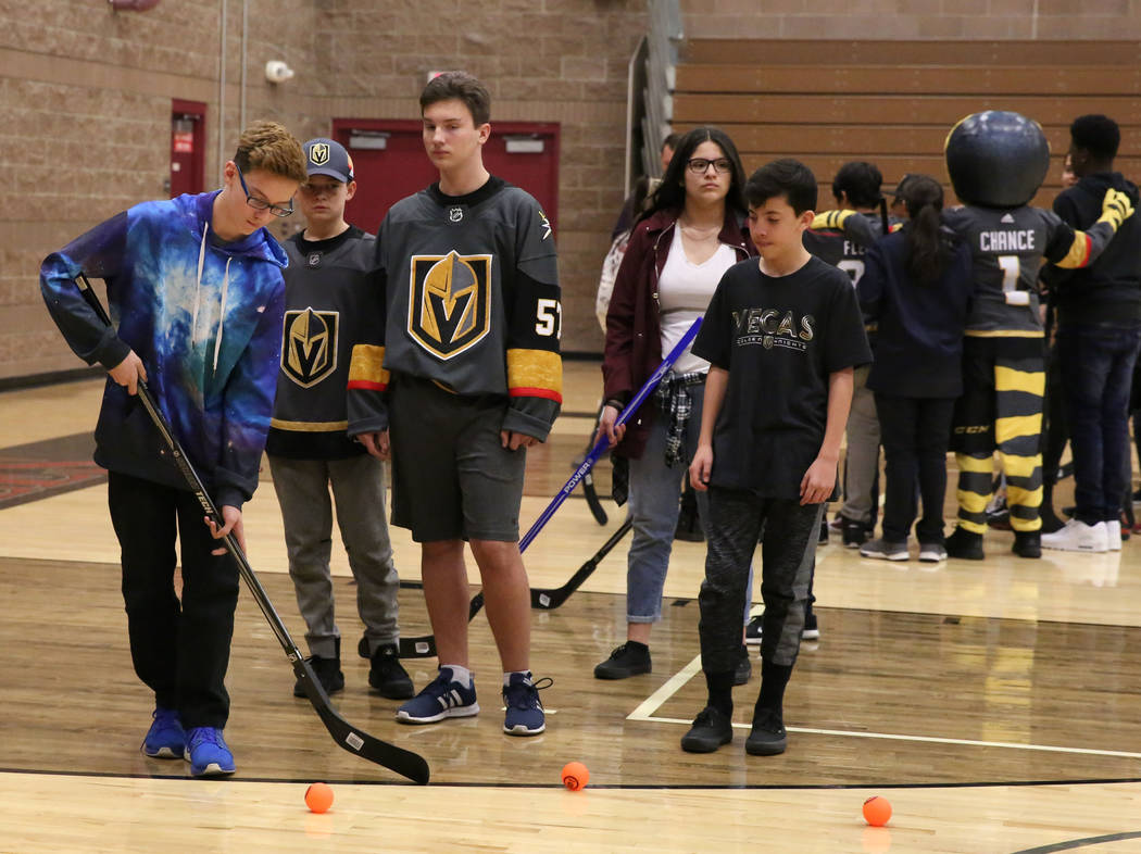 Rylie Barcomb, left, prepares to shoot to the goal at Walter Johnson Junior High School on Monday, Feb. 12, 2018, in Las Vegas. Vegas Golden Knights and Clark County School District will bring str ...