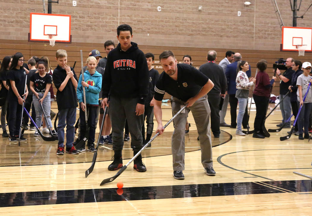 Matt Flynn, Vegas Golden Knights senior manager, youth hockey, right, demonstrates how to hit the target to Maddox Valoaga at Walter Johnson Junior High School on Monday, Feb. 12, 2018, in Las Veg ...