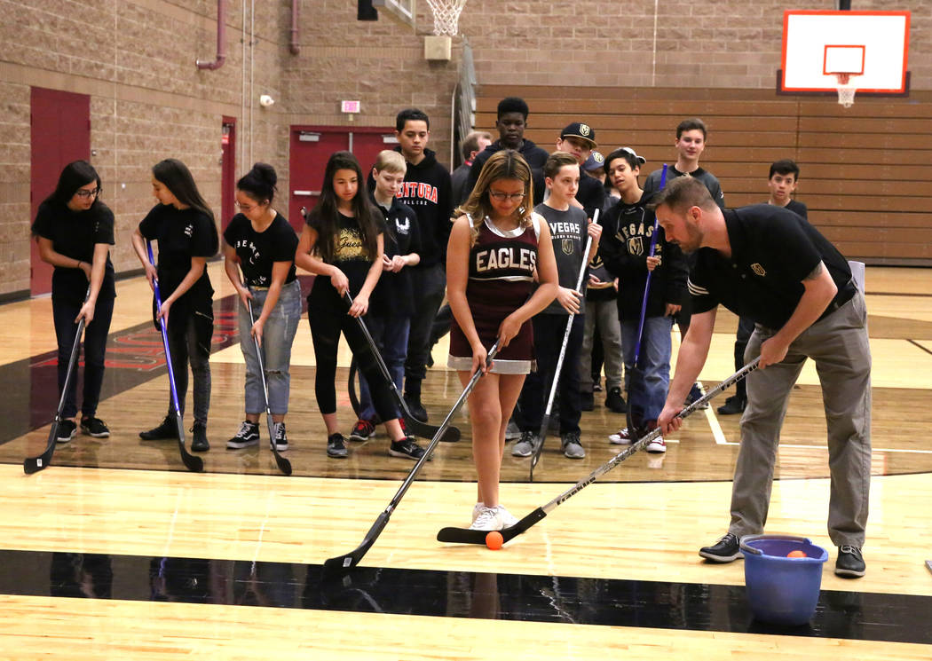 Matt Flynn, Vegas Golden Knights senior manager, youth hockey, right, demonstrates how to hit the target to Evelyn Murillo at Walter Johnson Junior High School on Monday, Feb. 12, 2018, in Las Veg ...