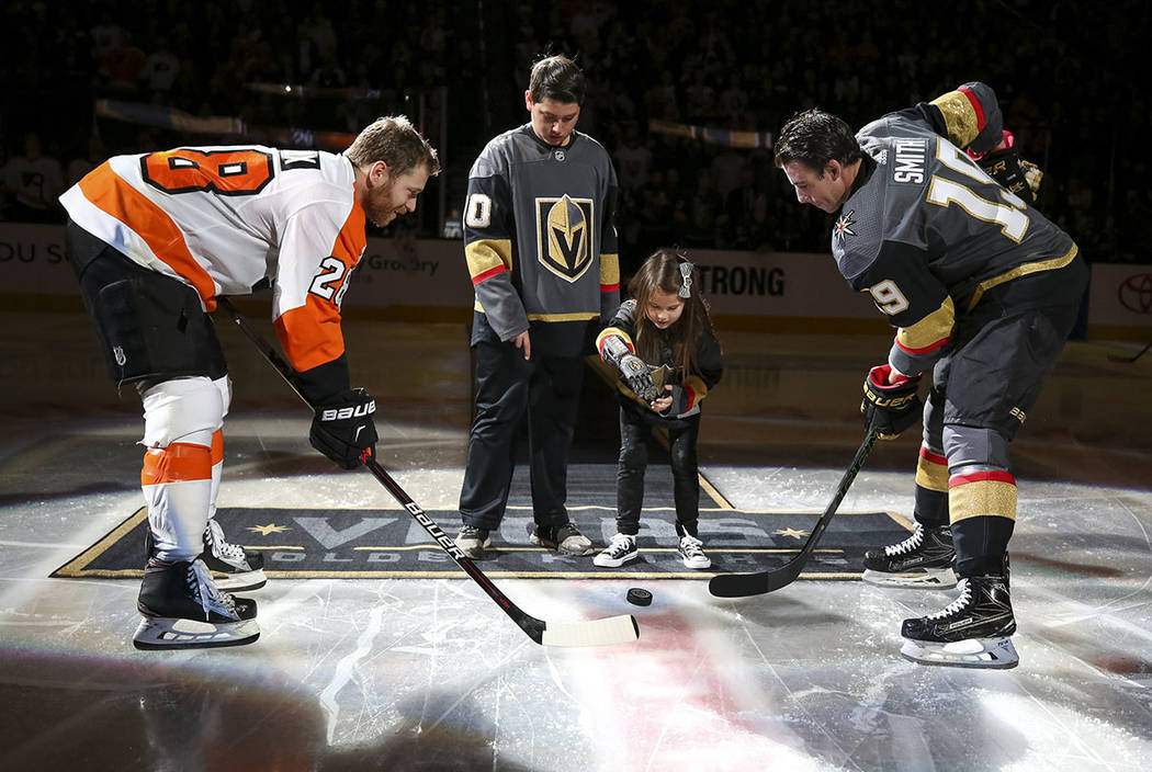 Hailey Dawson, center right, drops the puck for Philadelphia Flyers center Claude Giroux (28) and Vegas Golden Knights right wing Reilly Smith (19) before the start of an NHL hockey game between t ...