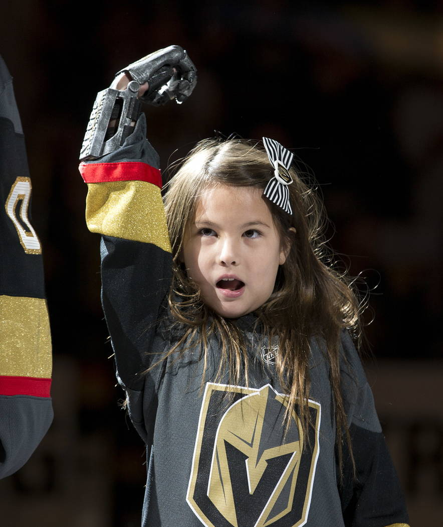 Hailey Dawson holds up her prosthetic hand before dropping the puck before the start of an NHL hockey game between the Vegas Golden Knights and the Philadelphia Flyers at T-Mobile Arena in Las Veg ...