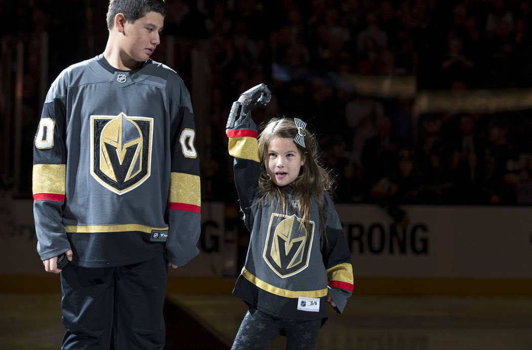 Hailey Dawson, right, holds up her prosthetic hand before dropping the puck before the start of an NHL hockey game between the Vegas Golden Knights and the Philadelphia Flyers at T-Mobile Arena in ...