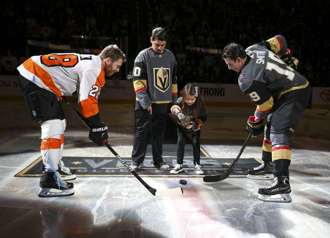 Hailey Dawson, center right, who has a 3-D prosthetic hand, drops the puck for Philadelphia Flyers center Claude Giroux (28) and Vegas Golden Knights right wing Reilly Smith (19) before the start  ...
