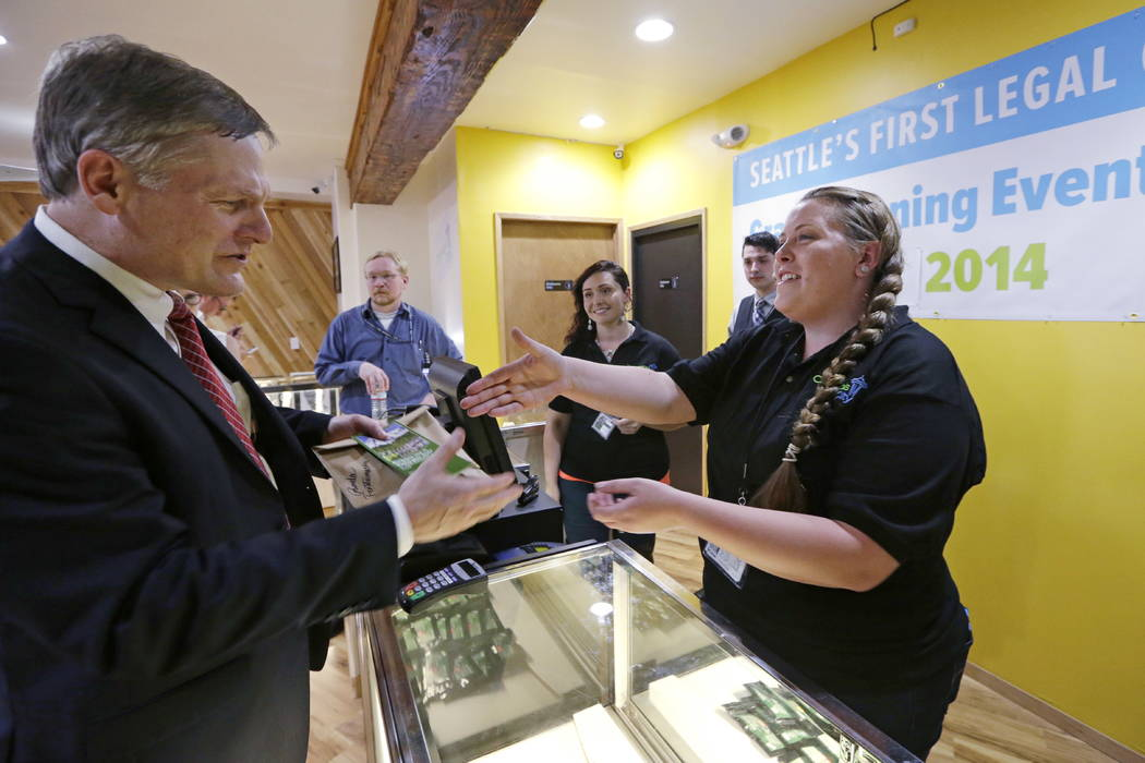 Seattle City Attorney Pete Holmes, left, shakes hands with clerk Pam Fenstermacher after purchasing marijuana at Cannabis City in Seattle in 2014. (AP Photo/Elaine Thompson, Pool, File)