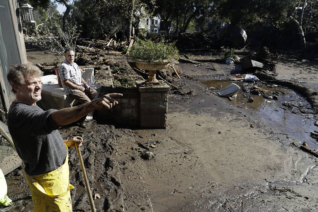 Bill Asher, left, and his friend Gil Loustalot survey storm damage to Asher's home in Montecito, Calif., last month. (AP Photo/Marcio Jose Sanchez, file)