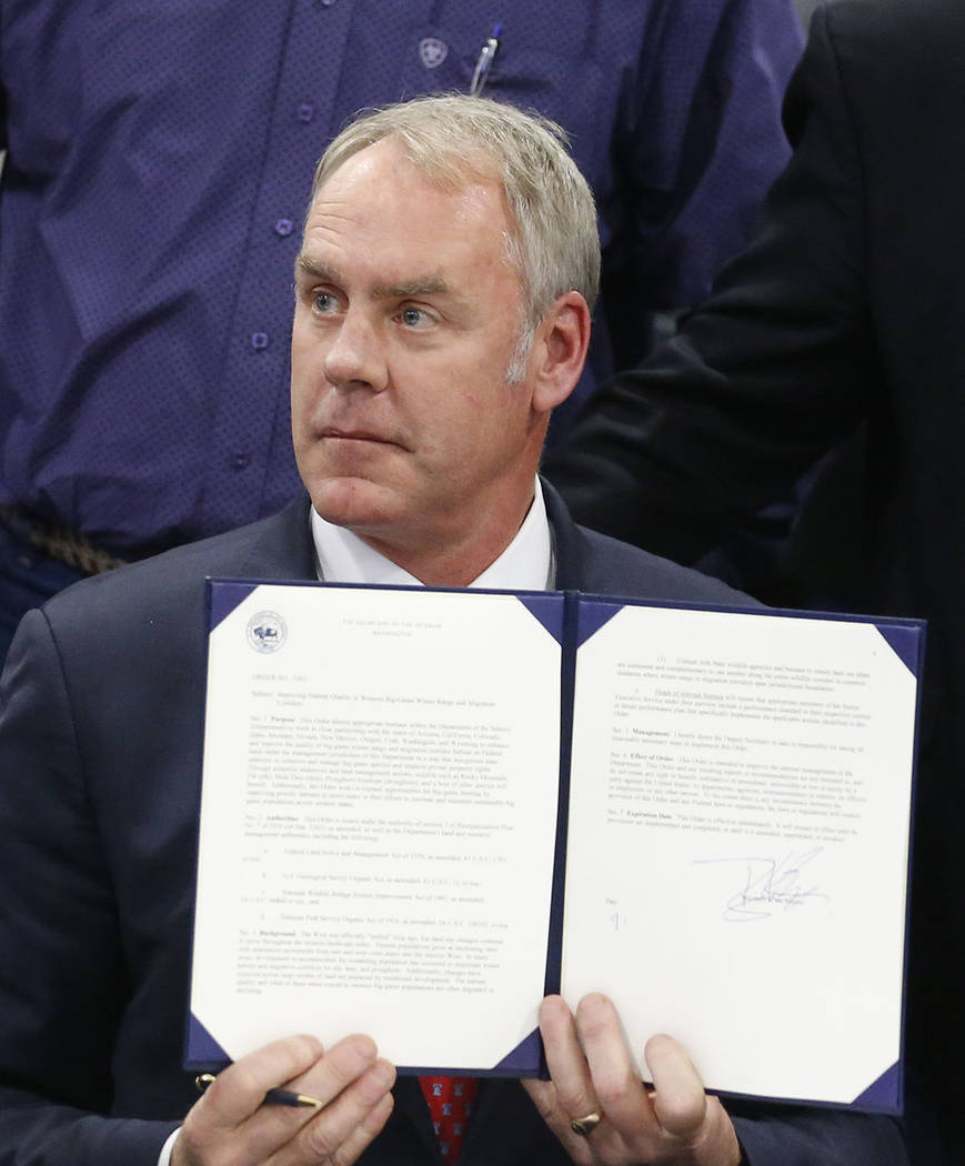 U.S. Interior Secretary Ryan Zinke holds up his signed Secretarial Order after announcing a wildlife initiative during the Western Conservation and Hunting Expo Friday, Feb. 9, 2018, in Salt Lake  ...
