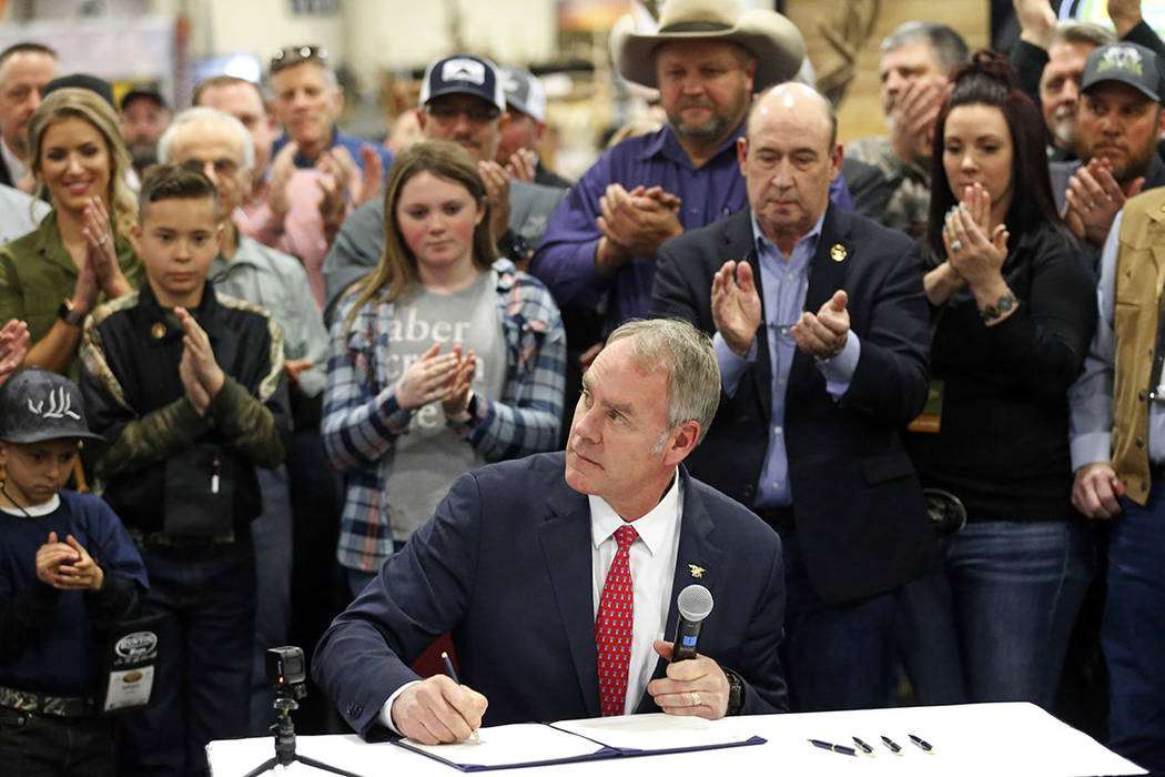 U.S. Interior Secretary Ryan Zinke holds signs a Secretarial Order after announcing a wildlife initiative during the Western Conservation and Hunting Expo Friday, Feb. 9, 2018, in Salt Lake City.  ...