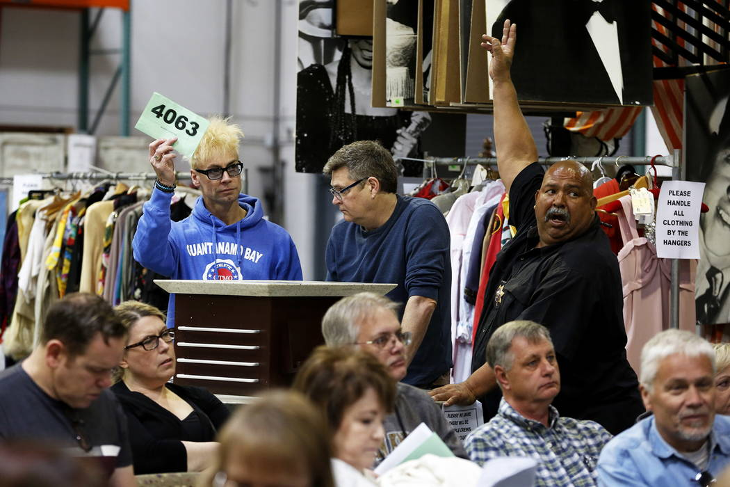 Murray Sawchuk, left, bids on Debbie Reynolds' vintage wall phone in an auction sale, which included almost 800 items collected by Reynolds and Carrie Fisher, at McManus Auctions in Las Vegas on S ...