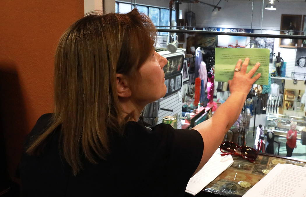 Carole Molchany, a certified antique appraiser, bids on Debbie Reynold's scrapbook of stars during an auction sale, which included almost 800 items collected by Reynolds and Carrie Fisher, at McMa ...