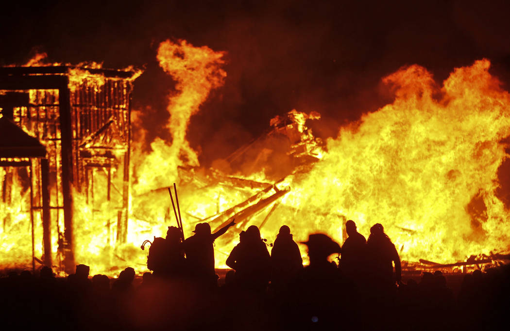 Attendees are silhouetted as the structure of the Man burns during Burning Man at the Black Rock Desert north of Reno on Saturday, Sept. 3, 2016. Chase Stevens/Las Vegas Review-Journal Follow @css ...