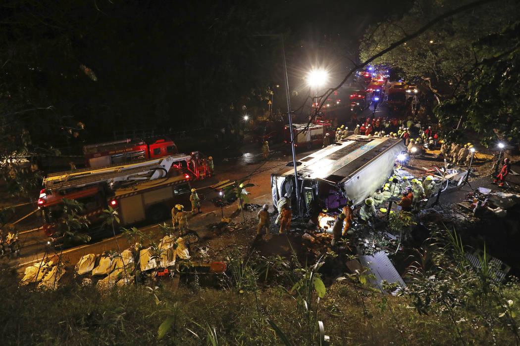 Firemen work at the scene of a bus crash in Hong Kong, Saturday, Feb. 10, 2018. (Apple Daily via AP)