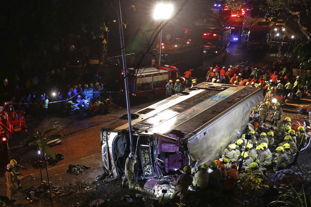 Firemen hurry to try to remove injured passengers from a double-decker lying on its side in Hong Kong, Saturday, Feb. 10, 2018. (Apple Daily via AP)