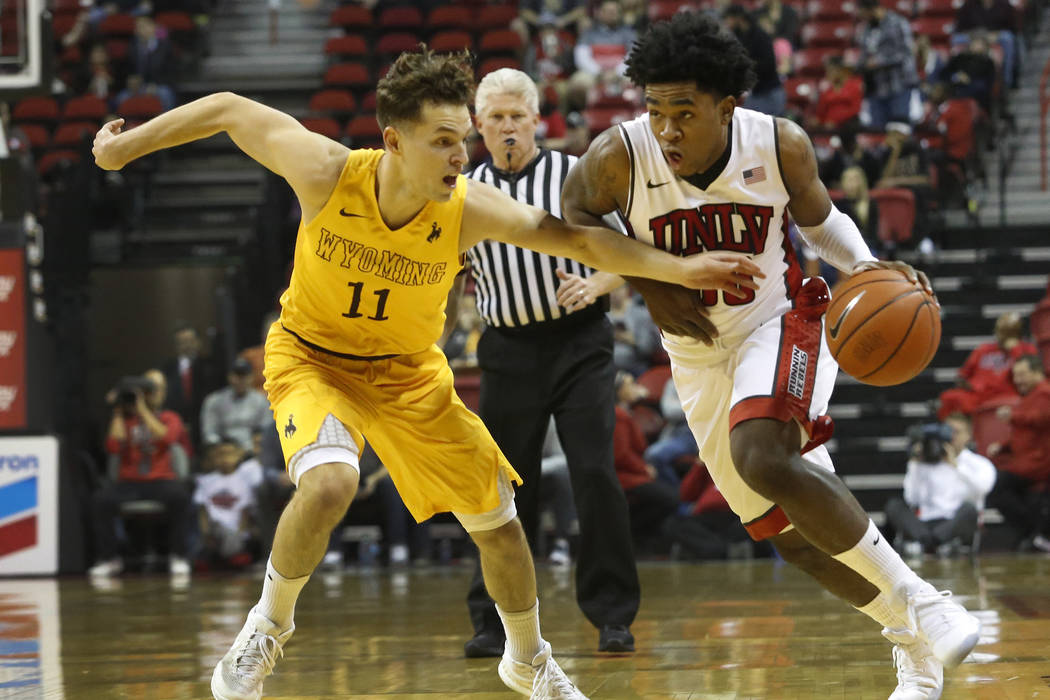UNLV guard Jovan Mooring (30) drives towards the hoop pass Wyoming guard Jeremy Lieberman (11) during the first half of a NCAA college basketball game against Wyoming at the Thomas & Mack Cent ...