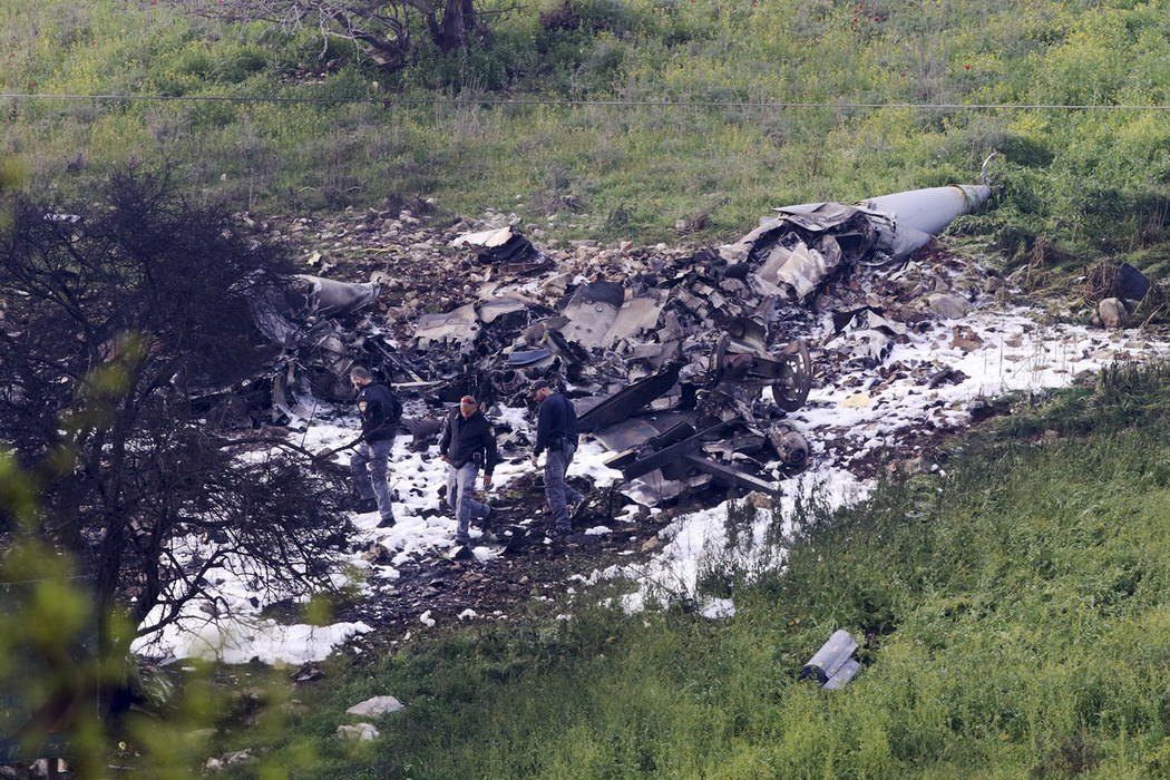 Israeli security stands around the wreckage of an F-16 that crashed in northern Israel, near kibbutz of Harduf, Saturday, Feb. 10, 2018. (AP Photo/Rami Slush)