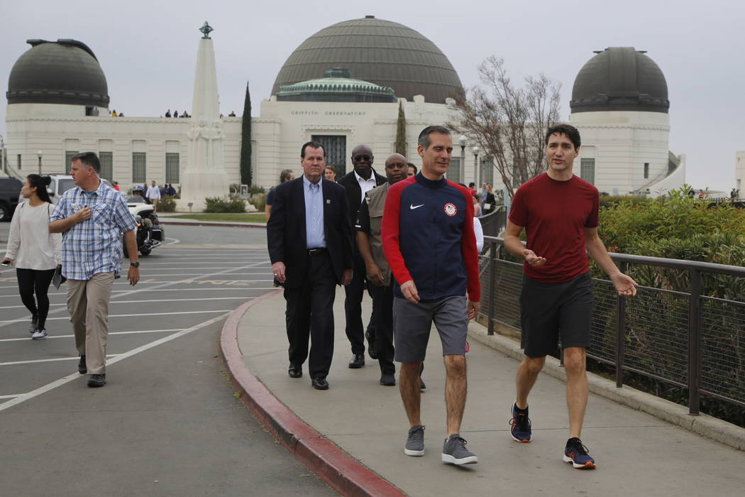 Canadian Prime Minister Justin Trudeau, far right, and Los Angeles Mayor Eric Garcetti, second from right, walk after holding a joint news conference at the Griffith Observatory Saturday, Feb. 10, ...